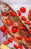 Baked trout with marinated tomatoes on a baking sheet
