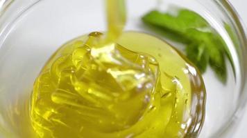 Miel vertida en tarro sobre fondo blanco.