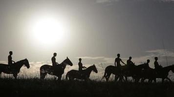Silhouettes of people on horses against sunrise