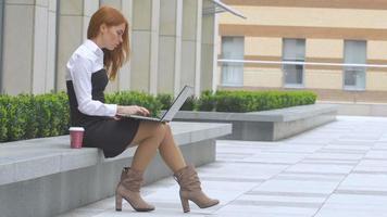 mulher ruiva usando laptop com uma xícara de café no terraço