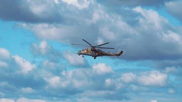 Attack helicopter Mi-24 flying on a background of clouds. Included audio