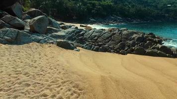 aérea: voando sobre as pedras na praia selvagem.