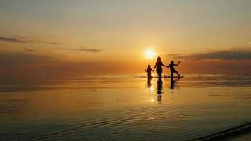 moeder met twee kinderen lachen in de zee bij zonsondergang, uit het water