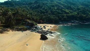 aérea: decolagem perto de uma grande rocha na praia selvagem de nui video