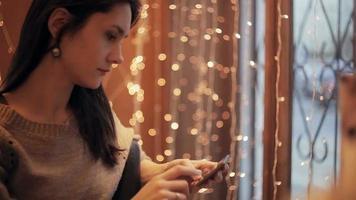 Mulher bonita usando smartphone no café