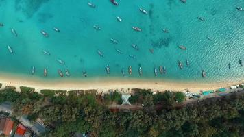 Aerial: Looking down at the Rawai beach with long tail boats. video