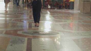 loira atraente de salto alto e vestida com um vestido preto longo caminha à noite em Milão