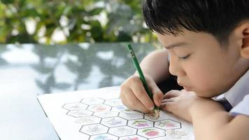 criança asiática sorridente estudando e fazendo sua lição de casa