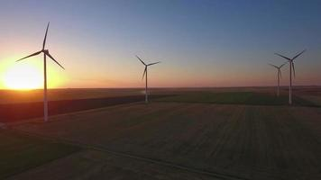 Aerial view of large wind turbines in a wind farm at sunset