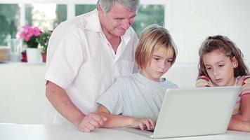 Child learning to use laptop with grandfather