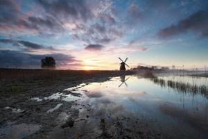 charming sunrise behind Dutch windmill photo