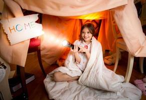 smiling girl playing with flashlight in house made of blankets