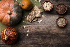 Rustic style pumpkins with seeds and cookies on wooden table