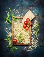 Pasta with ingredients for cooking on rustic background, top view