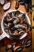 Fresh mussels in old colander on rustic wooden background