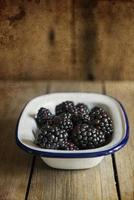 Blackberries in rustic kitchen setting with wooden background wi photo