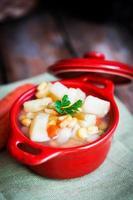 Sopa de fideos de pollo con verduras en un tazón sobre la mesa rústica foto