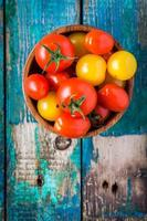 yellow and red cherry tomatoes in bowl on rustic table