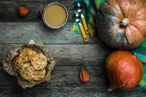 Rustic style pumpkins soup and cookies with seeds on wood