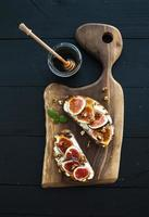 Sandwiches with ricotta, fresh figs, walnuts and honey on rustic