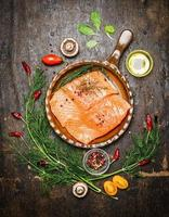 Salmon fillet in fried pan with ingredients for cooking