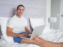 Happy man using laptop on bed