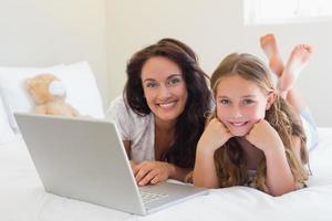 madre e hija, con, computador portatil, en cama foto