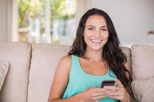 Pretty brunette texting with her smartphone