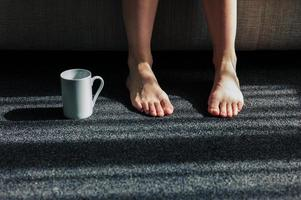 Mug next to feet of woman at home photo