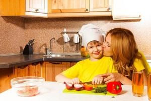Mother kisses son when he cuts vegetables photo