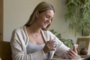 Woman using a smartphone in her home photo