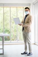 Entrepreneur wears face mask standing and holding laptop