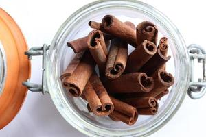 A bundle of cinnamon sticks in a glass jar