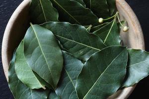 hojas de laurel en un cuenco de madera foto