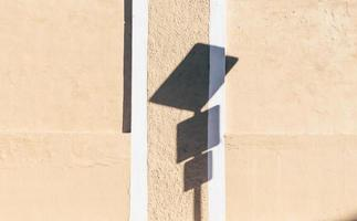 Road signage shadow on wall during the day