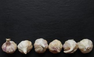 Cabezas de ajo sobre fondo de pizarra foto