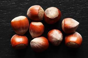 Handful of whole hazelnuts on slate background
