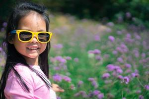 Little Asian girl in pink dress wearing sunglasses
