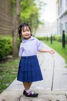 Portrait of happy little girl in Thai school uniform