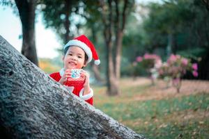 Little Asian girl in red Santa Claus costume