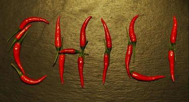 Red hot peppers spelled on slate background