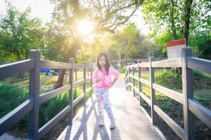 niña asiática de pie sobre un puente de madera