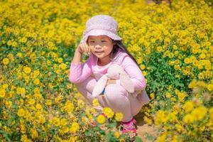 Little Asian girl in a pink dress in a flower garden photo