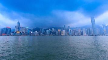 Hong Kong Victoria Harbour Cityscape Day To Night Time Lapse Of HongKong City, China (tilt up)