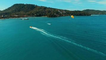 Aerial: Speed boat with parachute near the Patong beach.