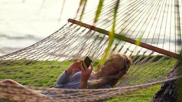 jovem rindo usando telefone móvel inteligente enquanto relaxa em uma rede à beira-mar entre as palmeiras ao pôr do sol no Havaí.