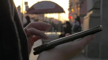 In Saint-Petersburg, Russia on evening street a girl working on mobile phone video