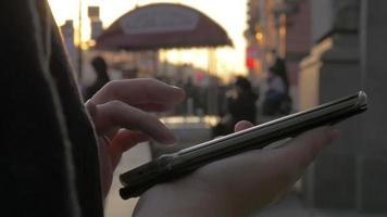 em São Petersburgo, Rússia, na rua à noite, uma garota trabalhando no celular