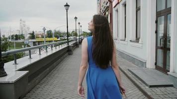 Hermosa mujer joven en vestido azul caminando en la ciudad con bolsas de compras, mira a su alrededor, tiro de cámara lenta