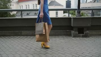 legs slender young woman, walking in the city down the street with shopping bags, side view, slow mo, stedicam shot video
